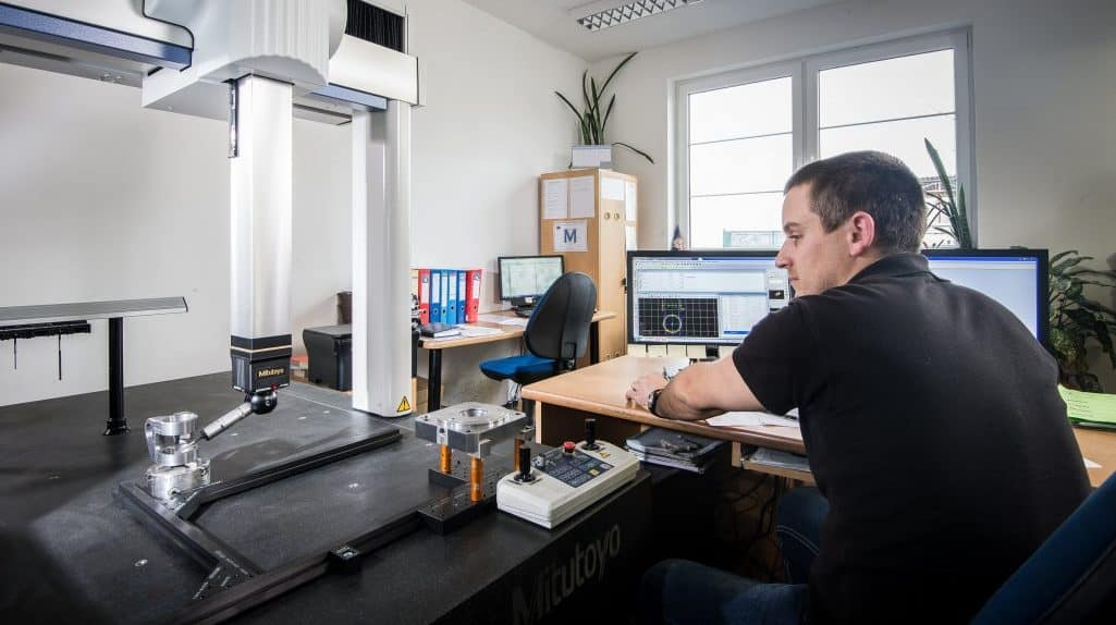 man measuring aluminium part using coordinate measuring machine (CMM)