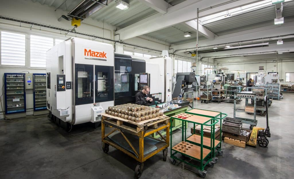 Mazak 5 axis cnc machine in a factory with a man inspecting parts