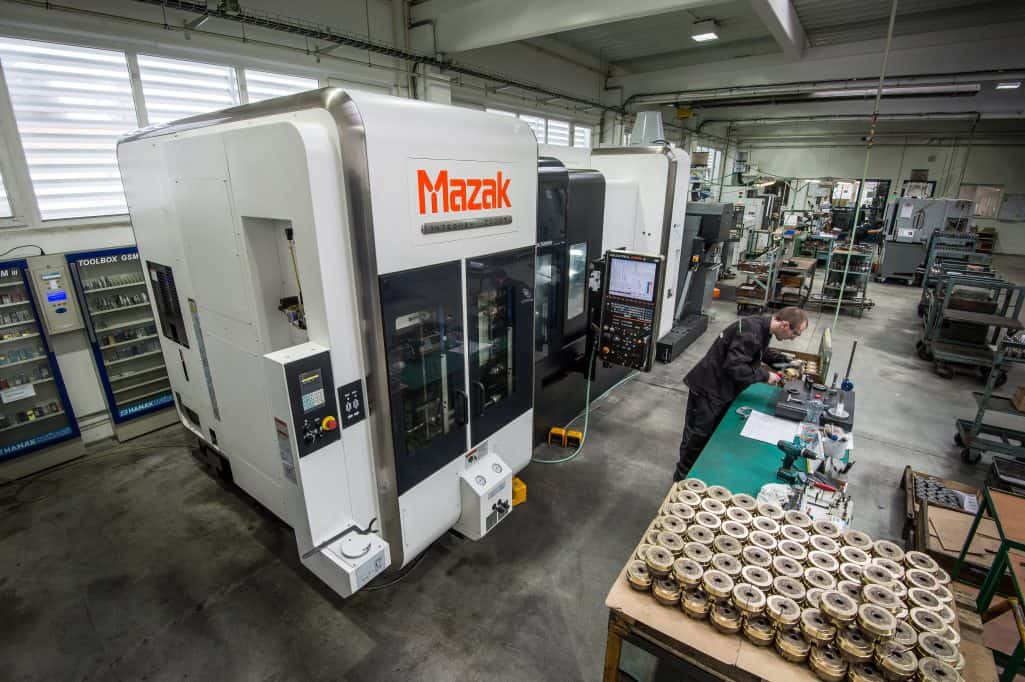 overhead view of mazak 5 axis cnc machining centre and high precision parts on a table in a factory