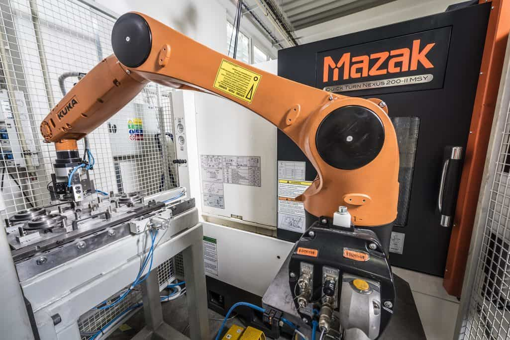 kuka robotic arm loading a cnc machine with an aluminium part
