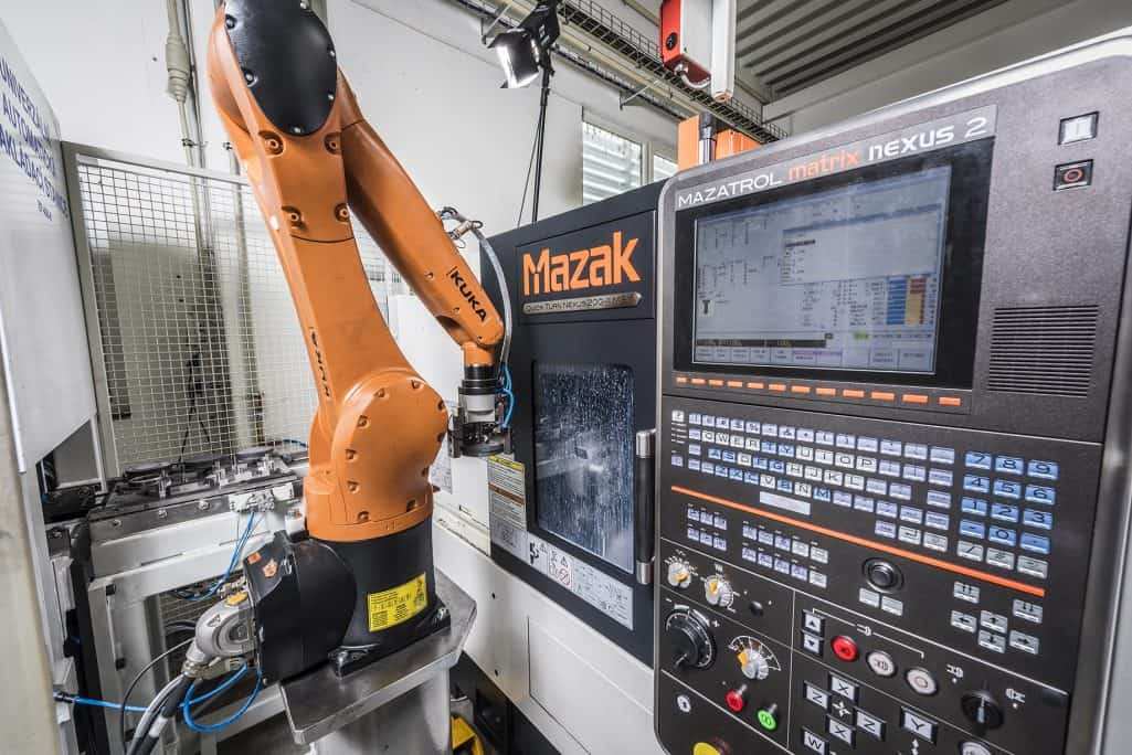 kuka robotic arm unloading a mazak cnc machine with an aluminium part in factory