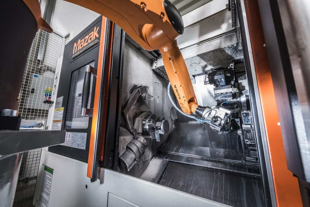 kuka robotic arm loading a mazak cnc machine with an aluminium part in factory