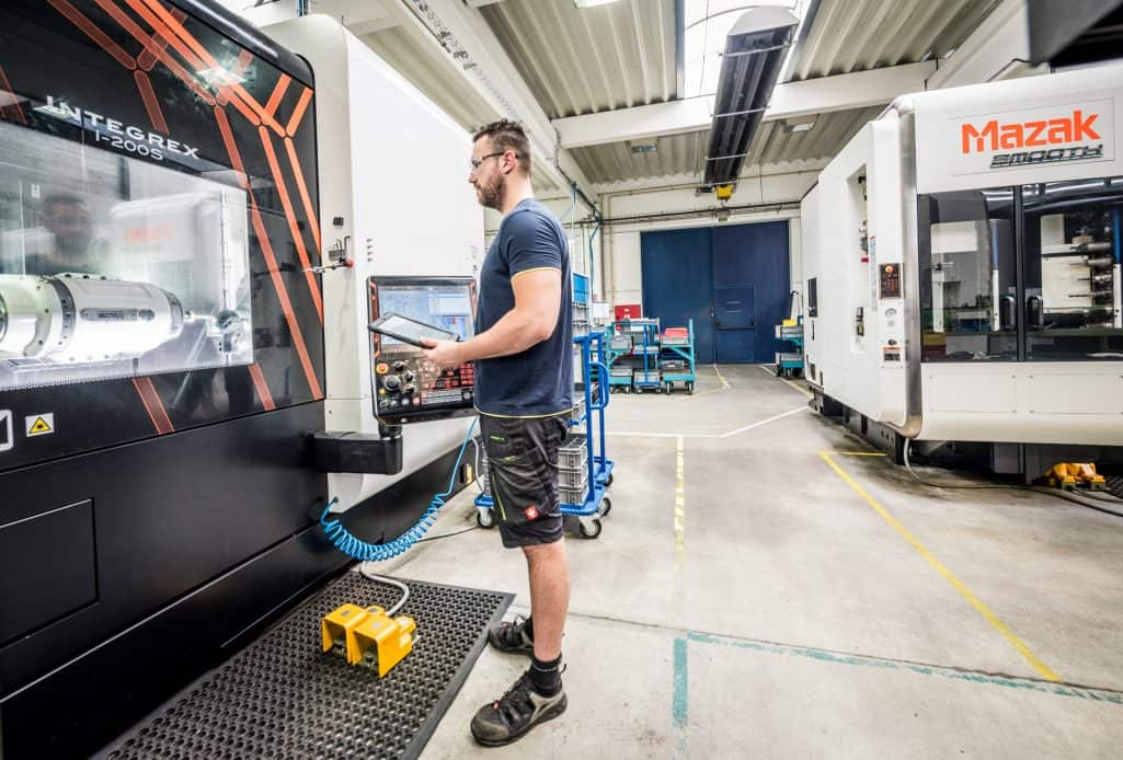 man wearing shorts watching a Mazak CNC machine holding a pendant in a factory